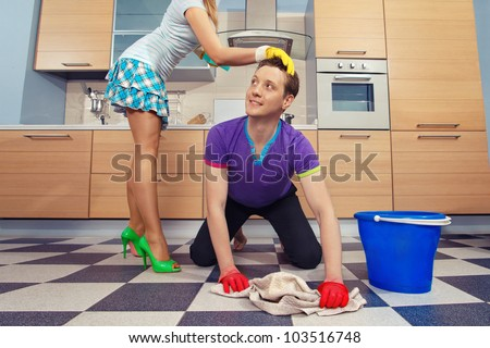 Young man cleaning floor and looking at her girlfriend