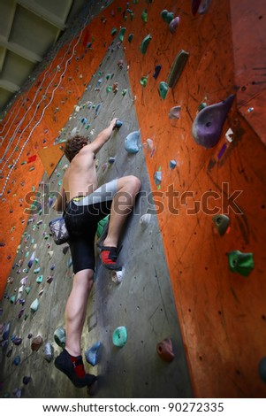 Young man climbing indoor wall