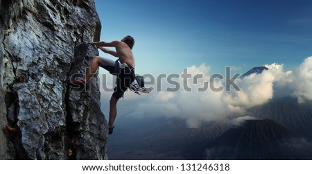 Young man climbing natural rocky wall with volcanoes on the background