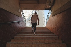 Young man climbing stairs in pedestrian subway, going to the city. Fit boy rises from the urban underpass to a building