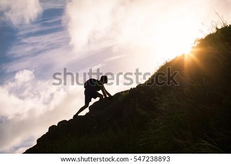 Young man climbing up a mountain. Self improvement and life goals concept.