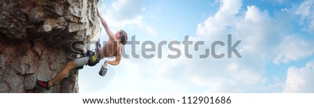 Young man climbing vertical wall with belay with blue cloudy sky on the background