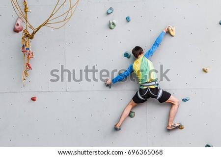 young man climbs up an...