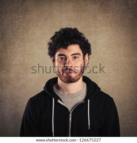 Young man close up portrait with perplexed expression against grunge background.