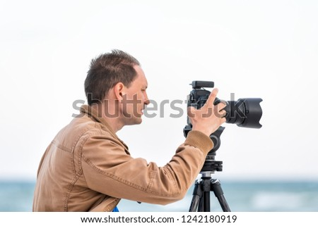 Young man closeup professional photographer taking pictures and video of beach sunset in Florida panhandle, with jacket, wind, beach waves, tripod