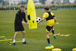 Young Man Coaching Soccer Boy. Coach on Training Session With Teenage Boy. Soccer Player Kicking Ball Standing on Stability Cushion on Grass Field. Football Player Improving Skills With Trainer