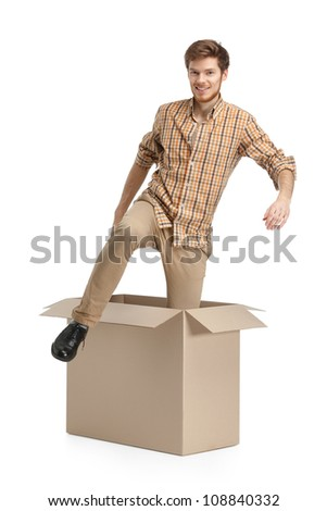 Young man comes out of the cardboard box, isolated, white background
