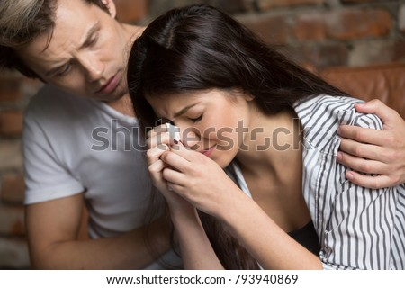 Young man comforting crying sad woman, caring friend consoling upset girl in tears, loving husband helping wife overcome problems or grief, compassion, empathy and support in relationships concept