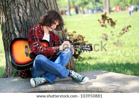 Young man composing for acoustic guitar in park