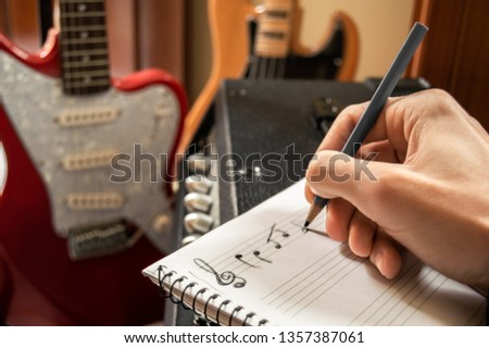 Young man composing music in a staff notebook with guitar and bass in the background. Musician writing in the music studio. Composing in treble clef.