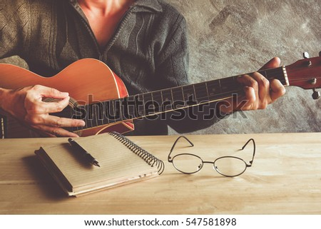 Young man composing the song with guitar on table