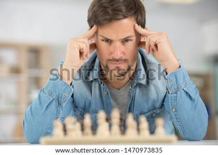 young man concentrating on a chess game