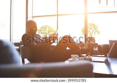 Young man confident entrepreneur is reading financial news via internet on portable touch pad, while is relaxing in cozy cafe. Male proud CEO is using digital tablet, while is waiting partner in bar