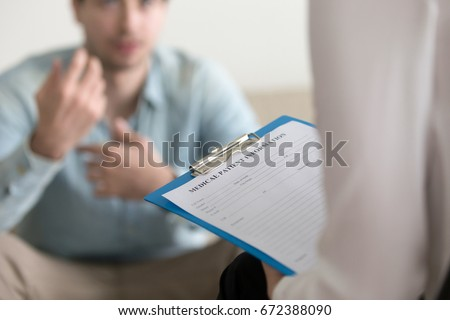 Young man consulting with medical doctor or psychologist, complaining about health, having problems. Focus on clipboard with patient card. Private health care facility reception, admission complaints