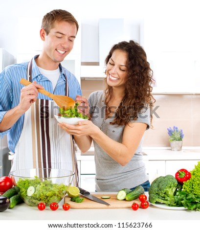Young Man Cooking. Happy Couple on a Kitchen at Home Eating Fresh Vegetable Salad.Diet.Dieting. Loose Weight Concept