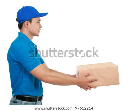 Young man courier in blue uniform stretching out his hand to give the packages