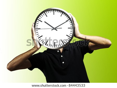 young man covering his face with a clock over green background