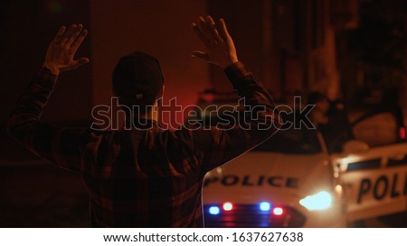 Young man criminal raises and puts hands behind his head surrenders to the police. Portrait of stressed male offender turning standing waiting for the arrest. Foto stock ©