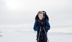 Young man cross country skiing in cold wintry conditions