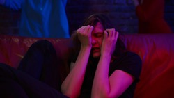 Young man crying hallucinating after drug overdose at club party. Close up portrait of drug addict guy having hysteria sitting on couch with people dancing on background in nightclub