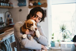 young man cuddling with his dog in kitchen