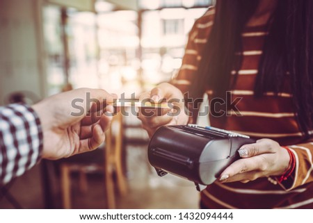 Young man customer making wireless or contactless payment using credit card. Asian people. #1432094444