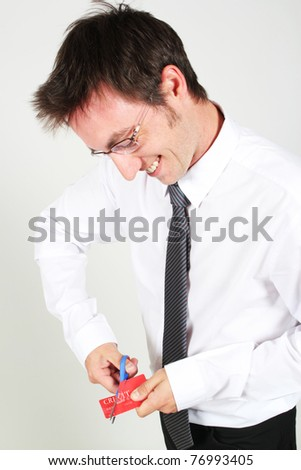 Young man cutting up a credit card