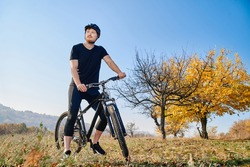 Young man cyclist enjoy the beautiful sunrise on autumn mounting forest trail