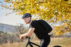 Young man cyclist enjoy the beautiful sunrise on autumn mounting forest trail. Concept of sport, mountain biking, active leisure