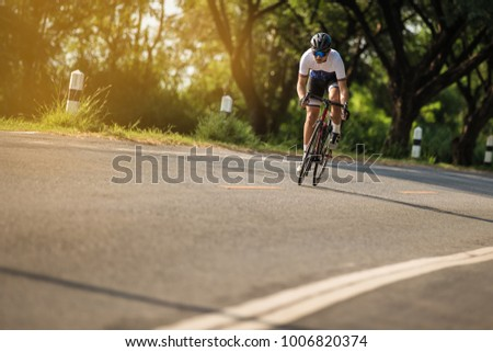 Young man Cyclist riding a bike on an open road to the sunset. #1006820374