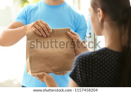 Young man delivering food to customer at doorway