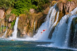 Young man diving from a big, beautiful waterfall. Dangerous environment, daredevil. Shot in Krka National Park, Croatia.