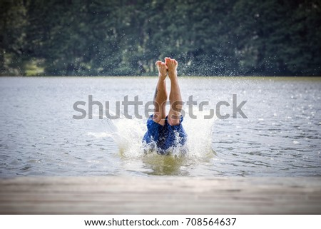 Young man diving into a lake. Careless and risky water jump. Summer vacation dangerous outdoor activity.