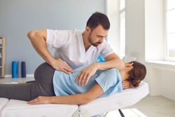 Young man doctor chiropractor or osteopath fixing lying womans back with hands movements during visit in manual therapy clinic. Professional chiropractor during work
