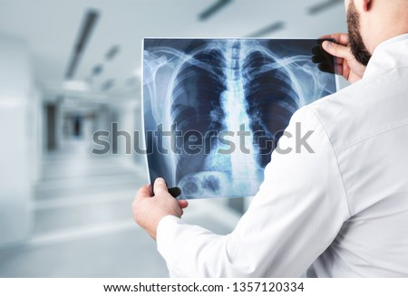 Young man doctor holding x-ray #1357120334