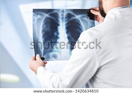 Young man doctor holding x-ray #1420634810