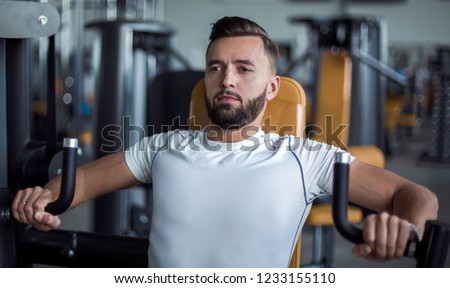 young man does weight training in the gym