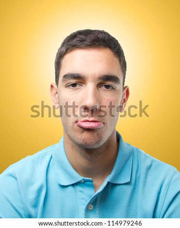 Young man doing a rare pose with his lips over light orange gradient