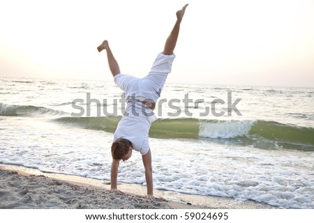 Young man doing cartwheels on the beach
