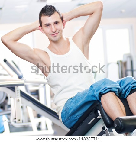 Young man doing exercises with sport equipment at gym club