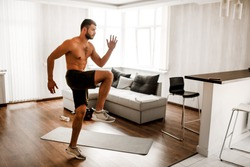 Young man doing exercising at home on the couch. Hardwoking t-shirtless guy sportsman in workout activity at his apartment. Trying to get better