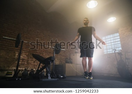 Young man doing hard exercise workout in gym interior with rope jump. Cinematic mood with dust, dramatic lightning and smoke. Active and healthy lifestyle.