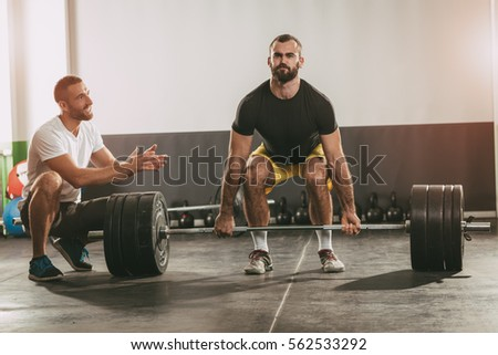 Young man doing workout with a personal trainer.