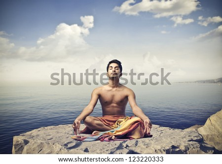 Young man doing yoga on a cliff