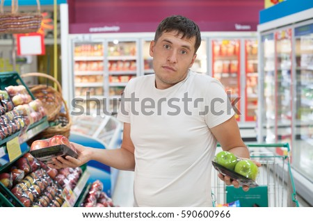 Young man don't know what to choose between red and green apples.
