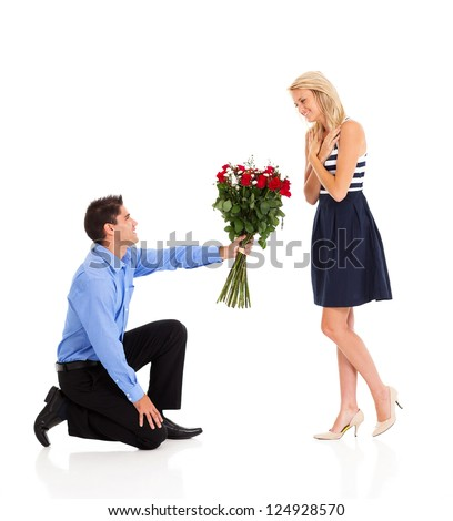 young man down on his knee to give bunch of roses to a woman - stock photo