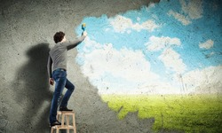 Young man drawing a cloudy blue sky on the wall