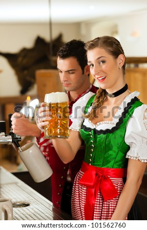 Young man drawing beer in restaurant or pub, he is the innkeeper