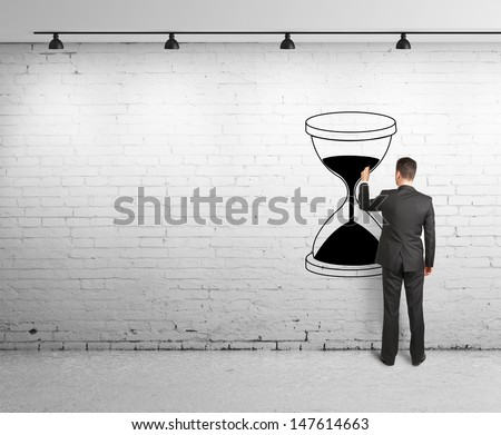 young man drawing hourglass on brick wal