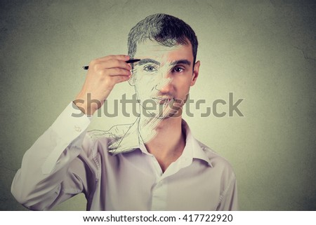 Young man drawing self portrait face, hiding true emotion isolated on grey wall background. Private life, identity concept.  ストックフォト ©